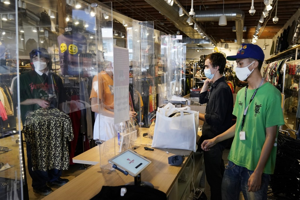 Employees check out customers at 2nd Street second hand store Monday, July 19, 2021, in the Fairfax district of Los Angeles. Los Angeles County has re...