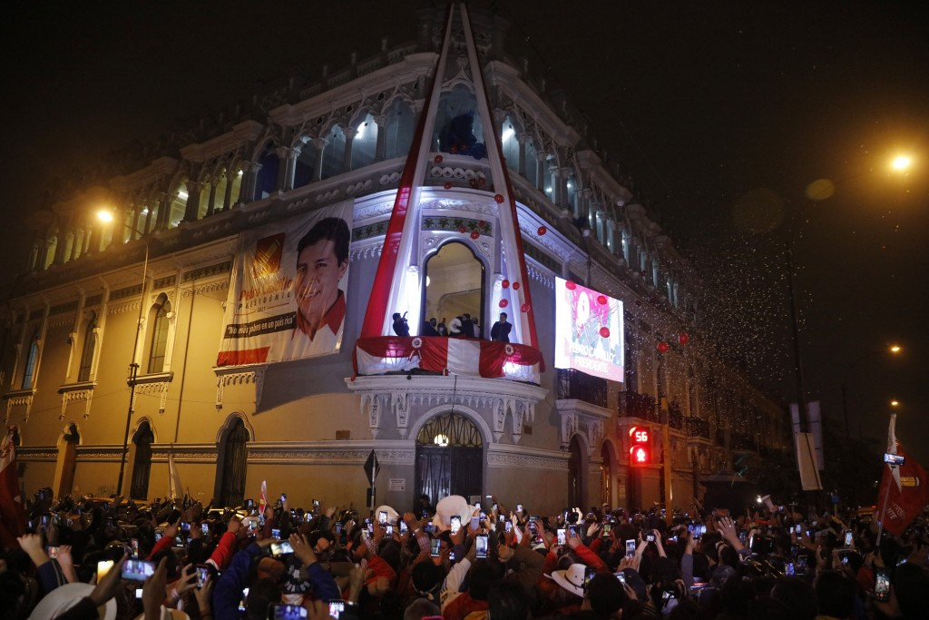 Pedro Castillo celebrates with his running mate Dina Boluarte after being declared president-elect of Peru by election authorities, from the balcony o...