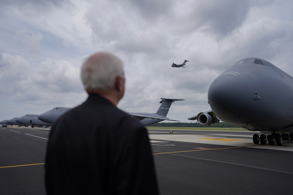 Air Force Mortuary Affairs Operations Senior Chaplain David Sparks looks at a C-5M Super Galaxy transport plane on the flightline at Dover Air Force B...