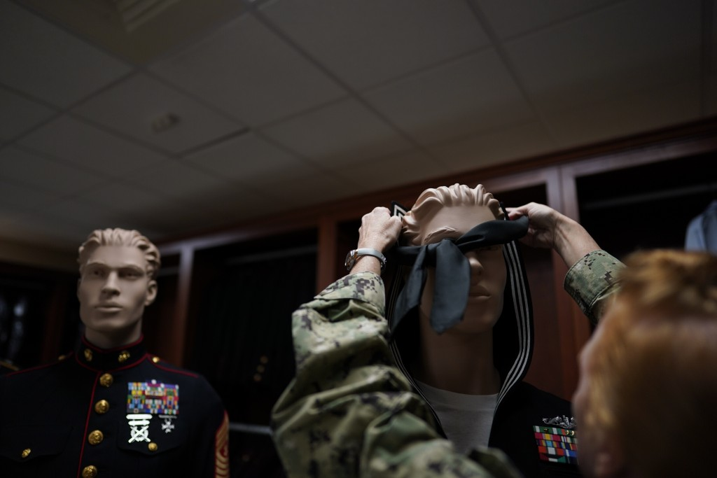 Chief Hospital Corpsman, United States Fleet Marine Forces, Jessica Zugzda places a neckerchief over the head of a mannequin to display a sample of a ...
