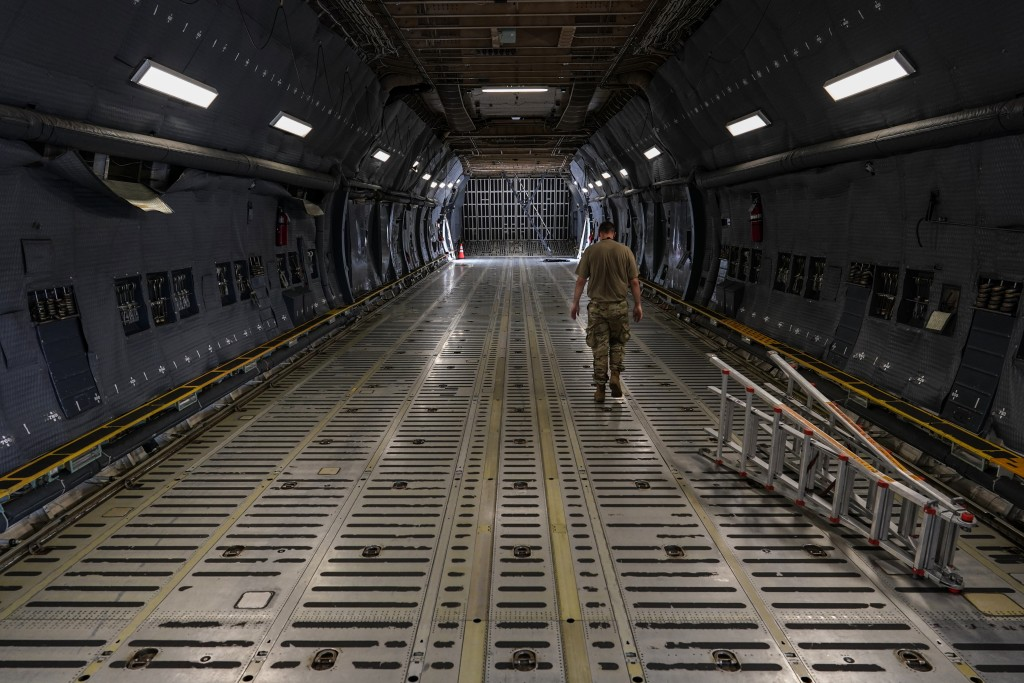 A crew member walks through an empty cargo hold of a C-5M Super Galaxy aircraft on the flightline at Dover Air Force Base, Del., Monday, June 21, 2021...