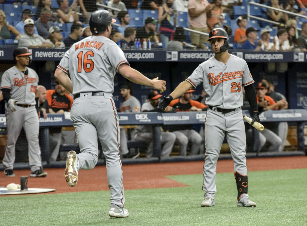 Baltimore Orioles' Ramon Urias (29) reaches to congratulate Trey Mancini (16) after Mancini scored on a sacrifice fly ball to center hit by Anthony Sa...