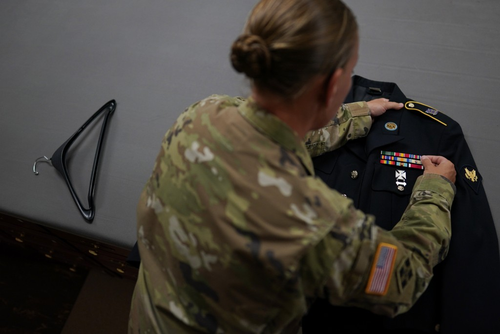 Sgt. 1st Class Nicole McMinamin, Army Liaison, Air Force Mortuary Affairs Operations, straightens a ribbon rack on a dress uniform in the uniform shop...