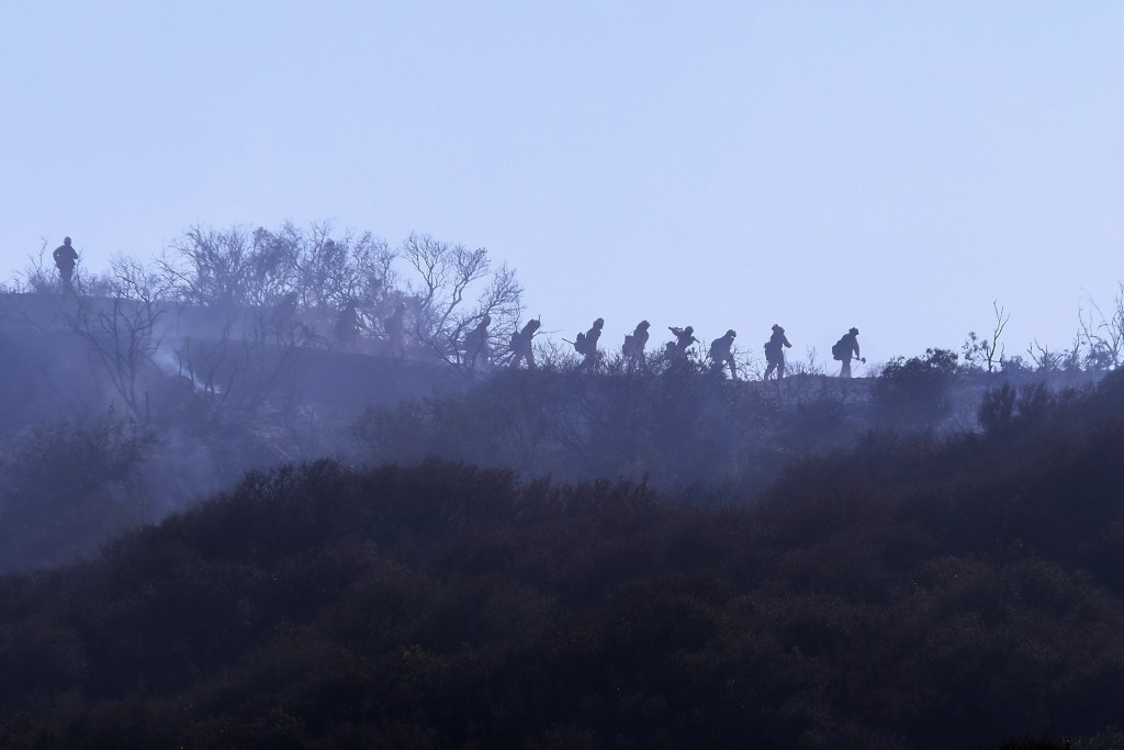 A hotshot hand crew walks in line during a wildfire in Topanga, west of Los Angeles, Monday, July 19, 2021. A brush fire scorched about 15 acres in To...