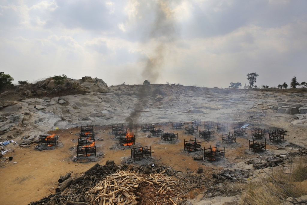 FILE - In this May 5, 2021, file photo, funeral pyres of twenty-five COVID-19 victims burn at an open crematorium set up at a granite quarry on the ou...