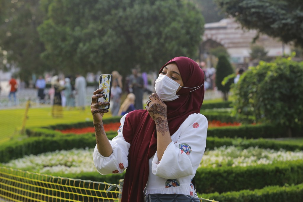 A woman takes selfie photos at the iconic Sultan Ahmed Mosque, better known as the Blue Mosque, in the historic Sultan Ahmed district of Istanbul, Tue...