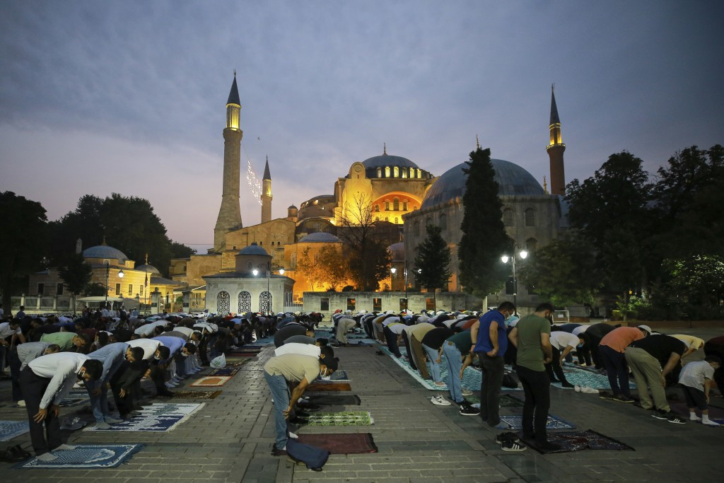 Muslims offer prayers during the first day of Eid al-Adha, outside the iconic Haghia Sophia in the historic Sultan Ahmed district of Istanbul, Tuesday...