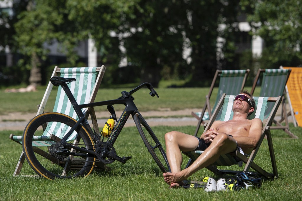 A man relaxes in the morning sunshine during a spell of hot weather in Green Park central London, Tuesday July 20, 2021. Temperatures are set to soar ...