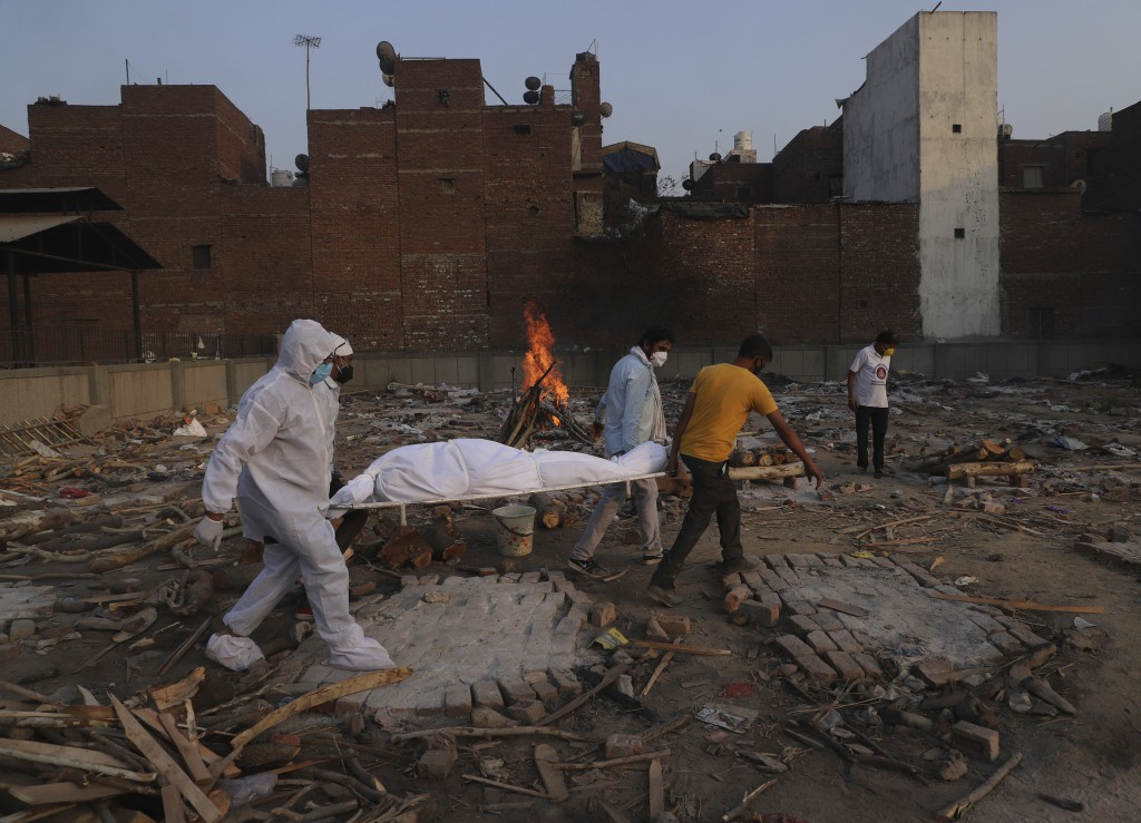 FILE - In this May 11, 2021, file photo, family members and volunteers carry the body of a COVID-19 victim for cremation in New Delhi, India. India's ...