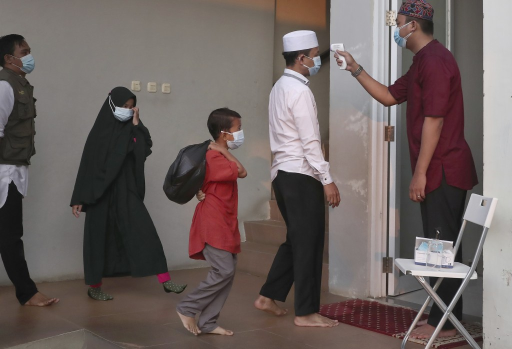 An official takes the body temperature reading of worshippers arriving for an Eid al-Adha prayer as to curb the spread of coronavirus during an Eid al...