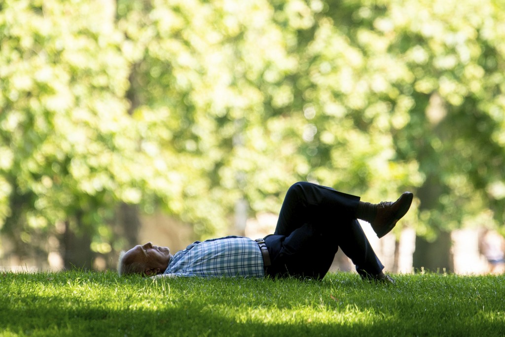 A man relaxes in the shade during a spell of hot weather in Green Park central London, Tuesday July 20, 2021. Temperatures are set to soar to swelteri...