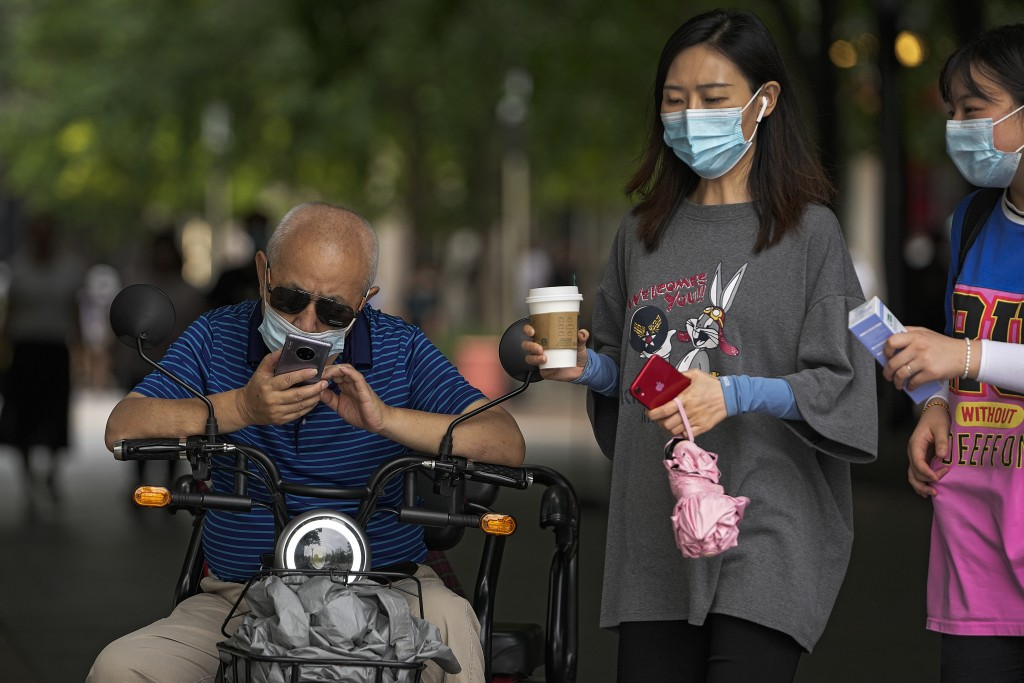 Women wearing face masks to help curb the spread of the coronavirus walk past a masked man browsing his smartphone on his bike in Beijing, Tuesday, Ju...