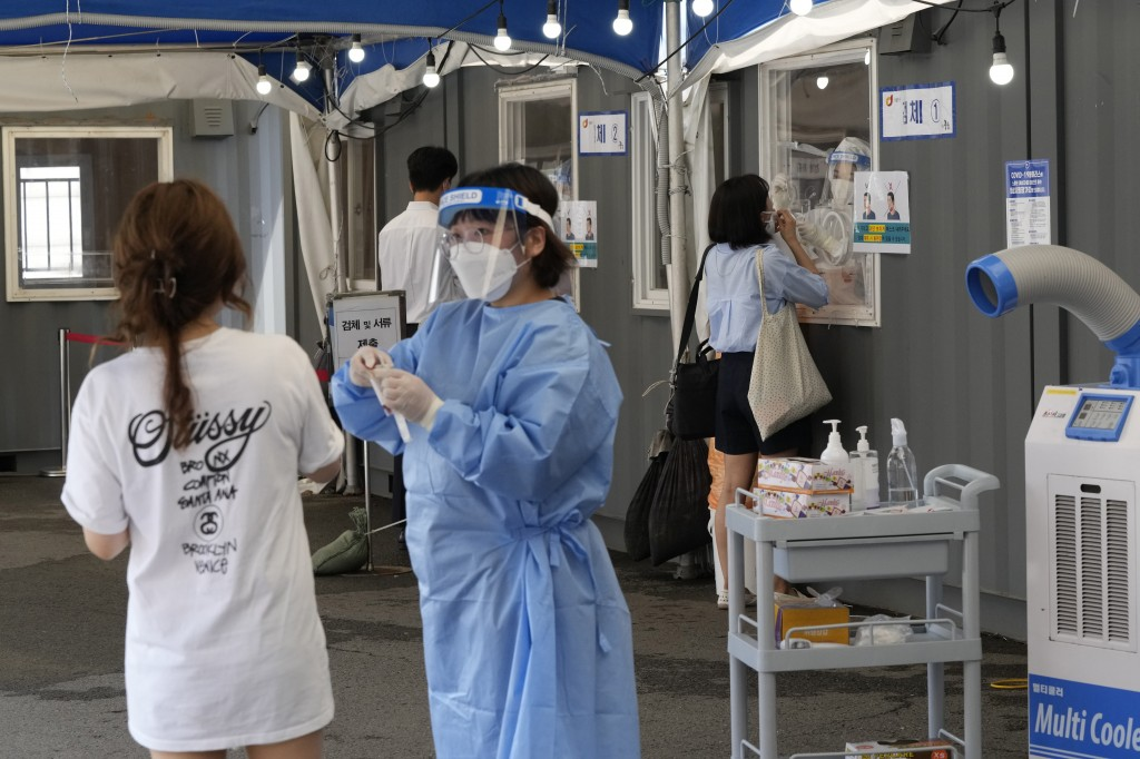 Medical workers takes nasal samples from residents for coronavirus tests at a makeshift testing site in Seoul, South Korea, Tuesday, July 20, 2021. (A...