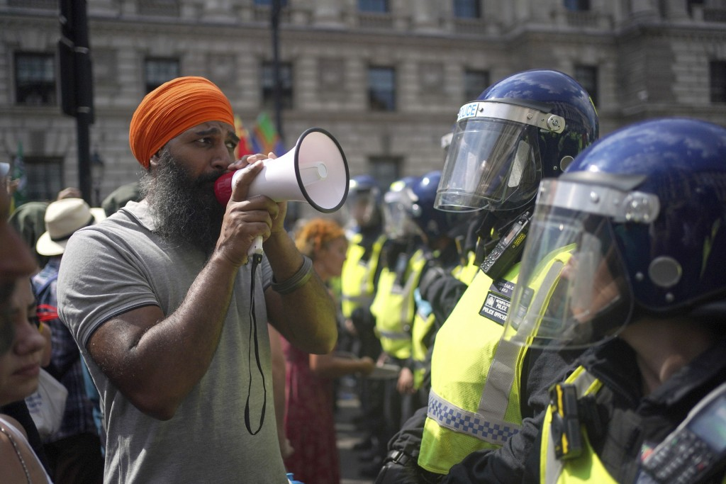 Police face anti-vaccination protesters during a demonstration in Parliament Square, London, Monday July 19, 2021, on the day the final legal coronavi...