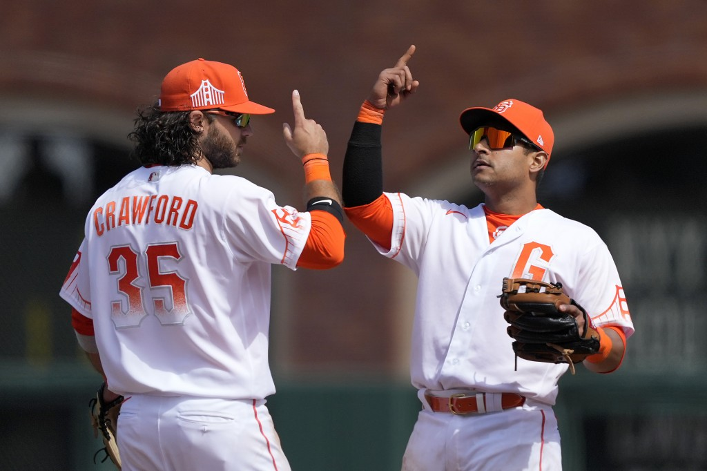 San Francisco Giants shortstop Brandon Crawford (35) and second baseman Donovan Solano, right, celebrate their victory over the Washington Nationals i...