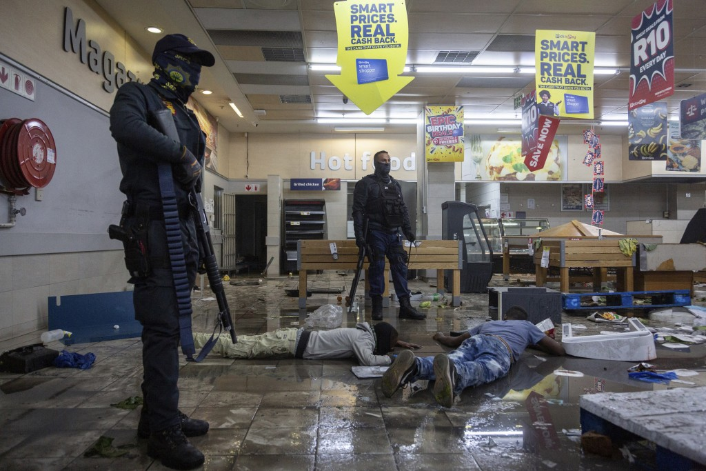 FILE - In this Monday, July 12, 2021 file photo, police stand over an arrested suspect looter in a shopping centre in Alexandra township, Johannesburg...