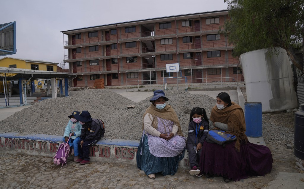 Mothers wait with their daughters on the campus of the Sacred Heart school, a public Catholic institution, for the first day of in-person classes to b...