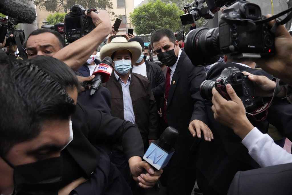 FILE - In this June 15, 2021 file photo, presidential candidate Pedro Castillo is surrounded by journalists as he arrives to his campaign headquarters...