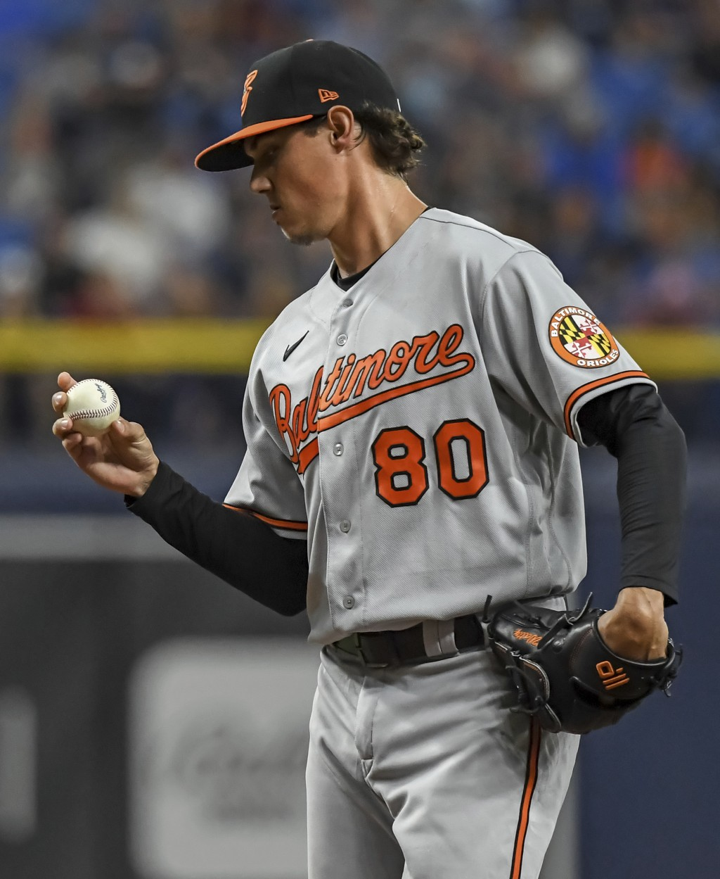 Baltimore Orioles starter Spenser Watkins looks over a new ball during the third inning of a baseball game against the Tampa Bay Rays, Monday, July 19...