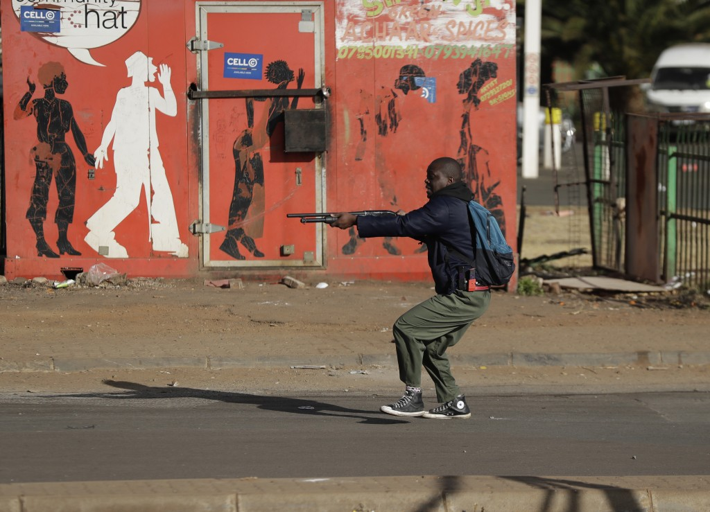 FILE - In this Tuesday July 13, 2021 file photo, metro police take aim on people who took part in a protest, at a shopping centre in Soweto, near Joha...