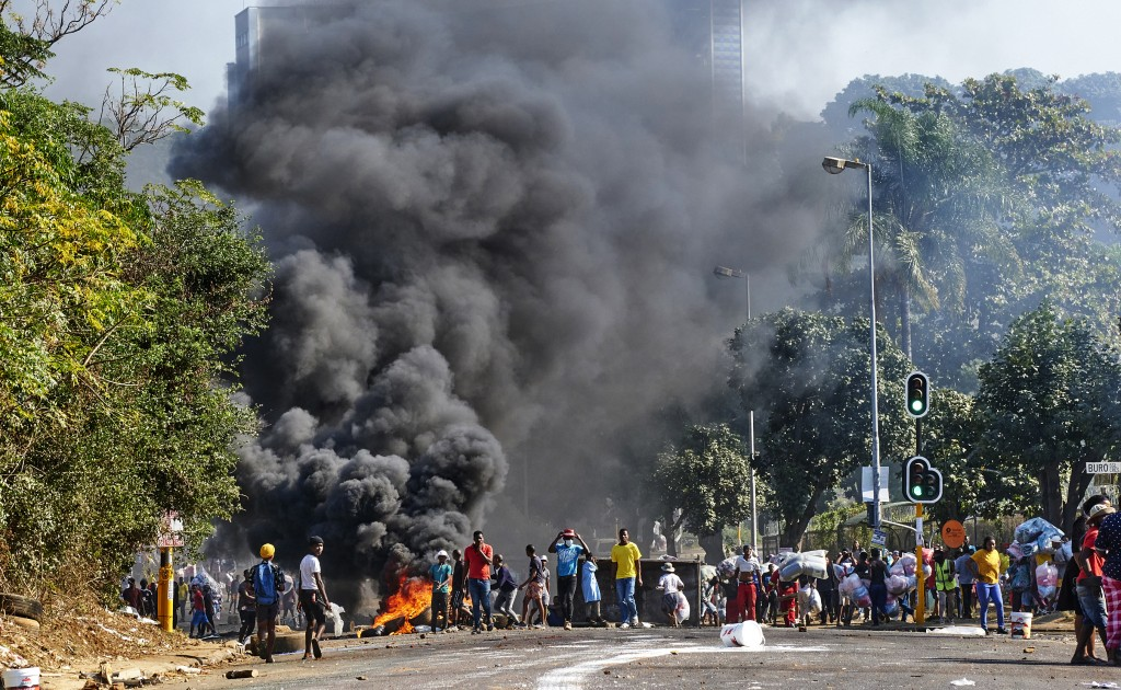 FILE - In this Monday July 12, 2021 file photo, looters outside a shopping centre alongside a burning barricade in Durban, South Africa. Former presid...