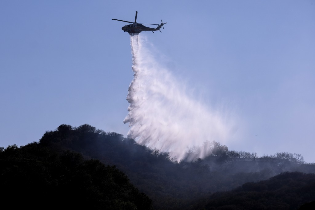 A A helicopter makes a water drop to put out hotspots in a wildfire in Topanga, west of Los Angeles, Monday, July 19, 2021. A brush fire scorched abou...