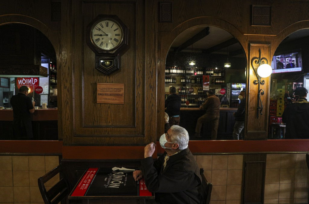 A customer wearing a mask to curb the spread of the new coronavirus, stands by for a waiter at La Union bar in Santiago, Chile, Monday, July 19, 2021....