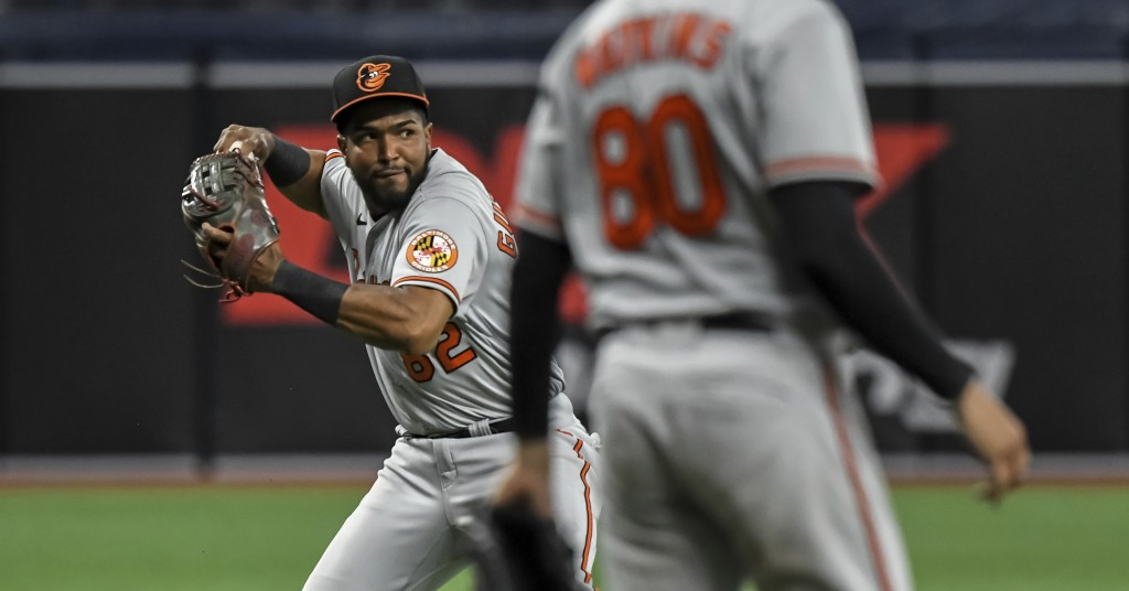 Baltimore Orioles third baseman Kelvin Guttierez , left, throws to first base after fielding a bunt-single hit by Tampa Bay Rays' Francisco Mejia duri...