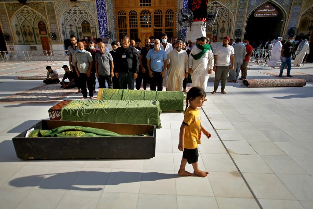 Mourners pray in a mosque before burying victims of a Monday bombing at a crowded Baghdad market busy with shoppers a day before the Muslim Eid al-Adh...