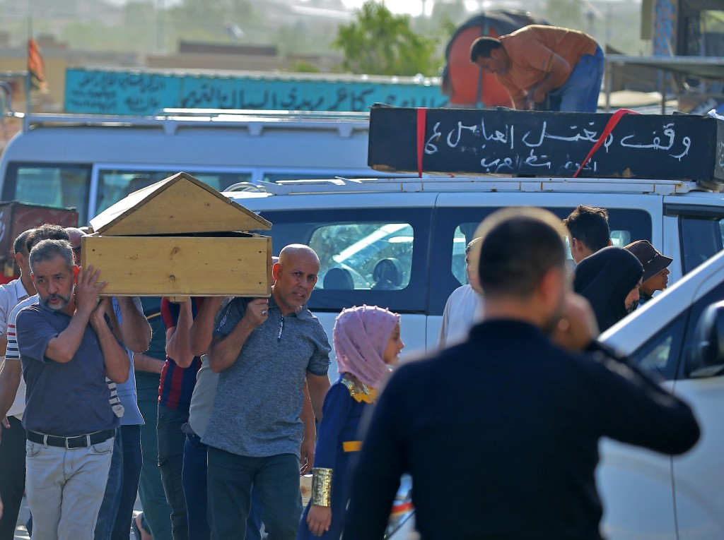 Mourners accompany victims of a Monday bombing at a Baghdad market that was busy with shoppers a day before the Muslim Eid al-Adha holiday, before the...