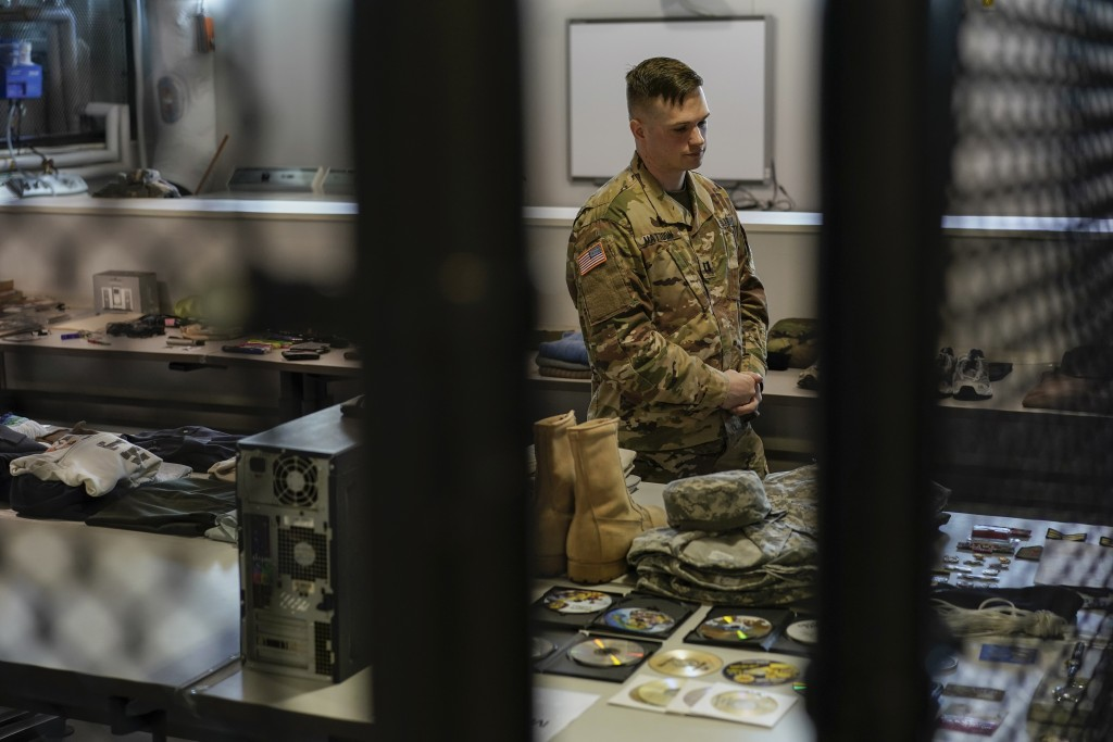 Army Capt. Geoffrey C. Mattoon stands among examples deceased service members belongings at the Joint Personal Effects Depot on Dover Air Force Base, ...
