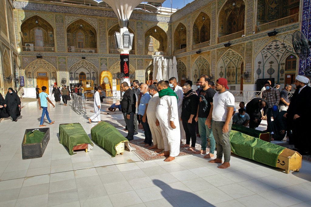 Mourners prepare to bury victims of a Monday bombing at a Baghdad market that was busy with shoppers a day before the Muslim Eid al-Adha holiday, in N...