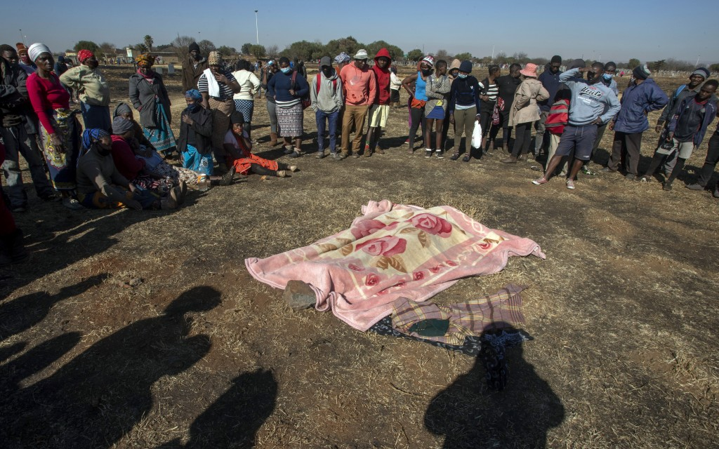FILE - In this Wednesday July 14, 2021 file photo, family members and residents surround the body of Vusi Dlamini, a 14-year-old boy who was shot outs...