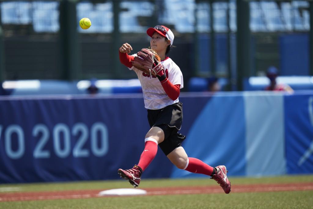 Japanese softball player Atsumi Mana throws the ball to first base during the team's training session at the Fukushima Azuma Baseball Stadium ahead of...