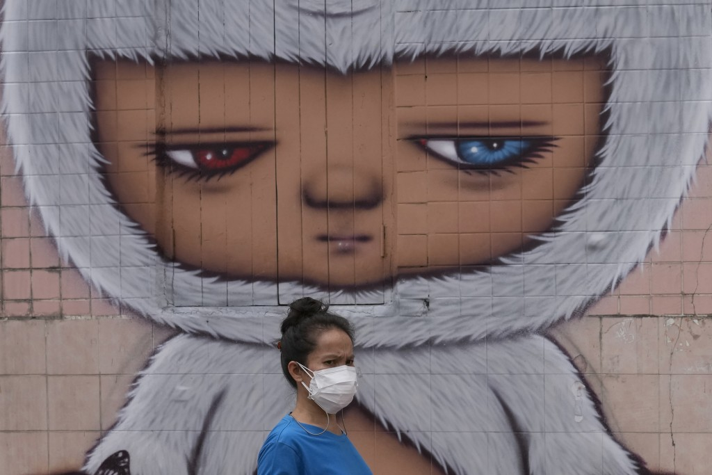A woman wearing a face mask to help curb the spread the coronavirus walks past wall art in Bangkok, Thailand, Tuesday, July 20, 2021. (AP Photo/Sakcha...