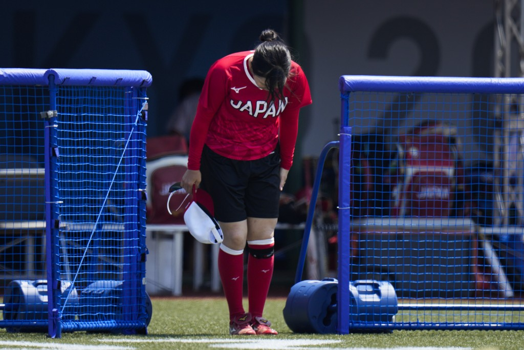 A Japanese softball player bows before walking onto the field during the team's training session at the Fukushima Azuma Baseball Stadium ahead of the ...