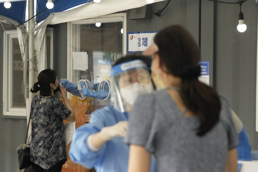 A medical worker in a booth takes a nasal sample from a woman at a makeshift testing site in Seoul, South Korea, Tuesday, July 20, 2021. (AP Photo/Ahn...