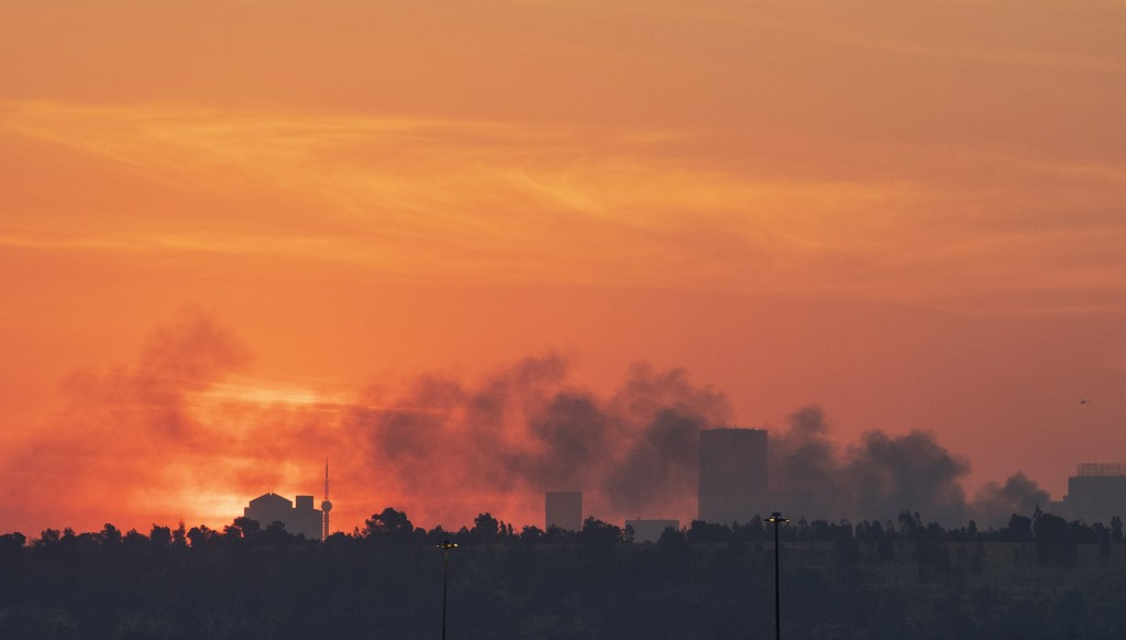 FILE - In this Sunday, July 11, 2021 file photo, smoke covers the Johannesburg skyline as people protest in downtown area, in Johannesburg, South Afri...