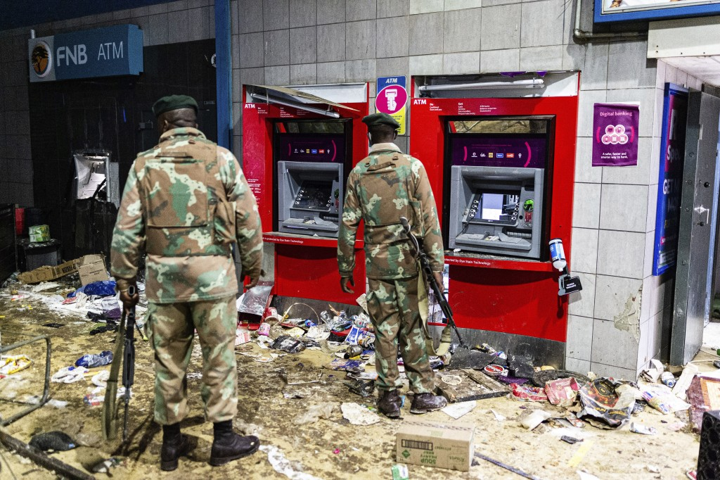 FILE - In this Monday, July 12, 2021 file photo, soldiers guard an autobank at the Bara taxi rank shops in Soweto, Johannesburg, Former president Jaco...
