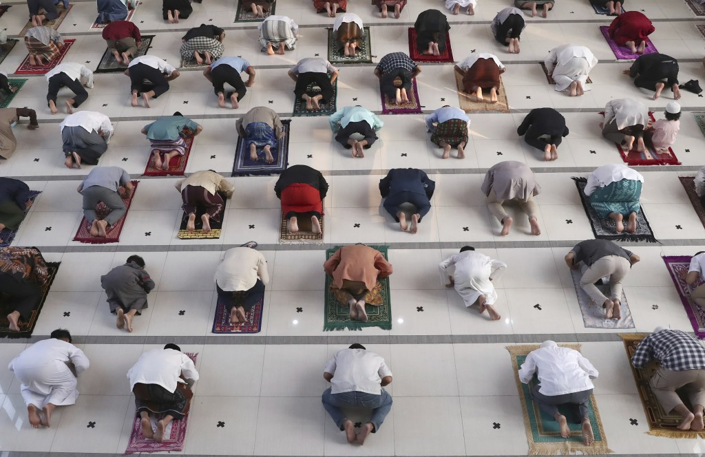 Muslims pray spaced apart as a precaution against the coronavirus outbreak during an Eid al-Adha prayer at Zona Madina mosque in Bogor, Indonesia, Tue...