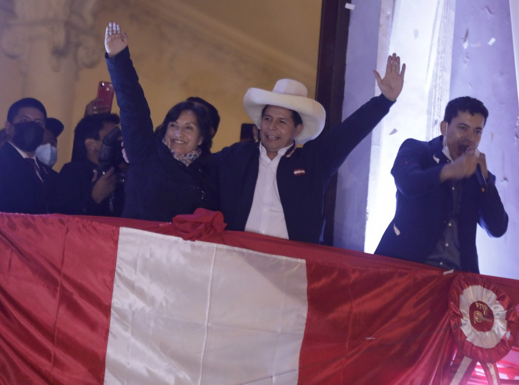 Pedro Castillo, center, celebrates with his running mate Dina Boluarte after being declared president-elect of Peru by election authorities, at his pa...