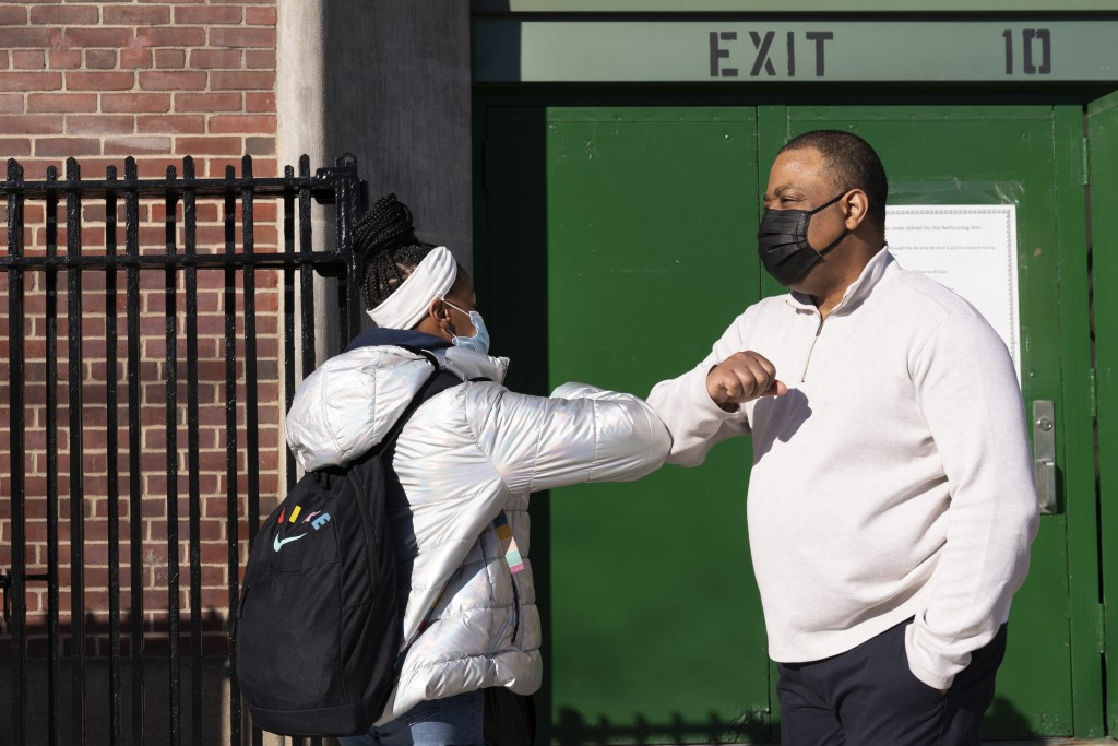 FILE - In this Feb. 25, 2021 file photo, Linsey Johnson, right, a dean at Meyer Levin Middle School, greets a student in New York. With COVID-19 cases...