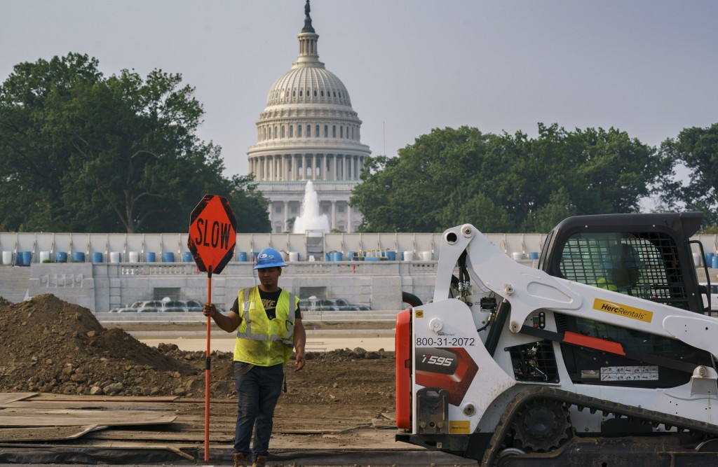 Workers repair a park near the Capitol in Washington, Wednesday, July 21, 2021, as senators struggle to reach a compromise over how to pay for nearly ...