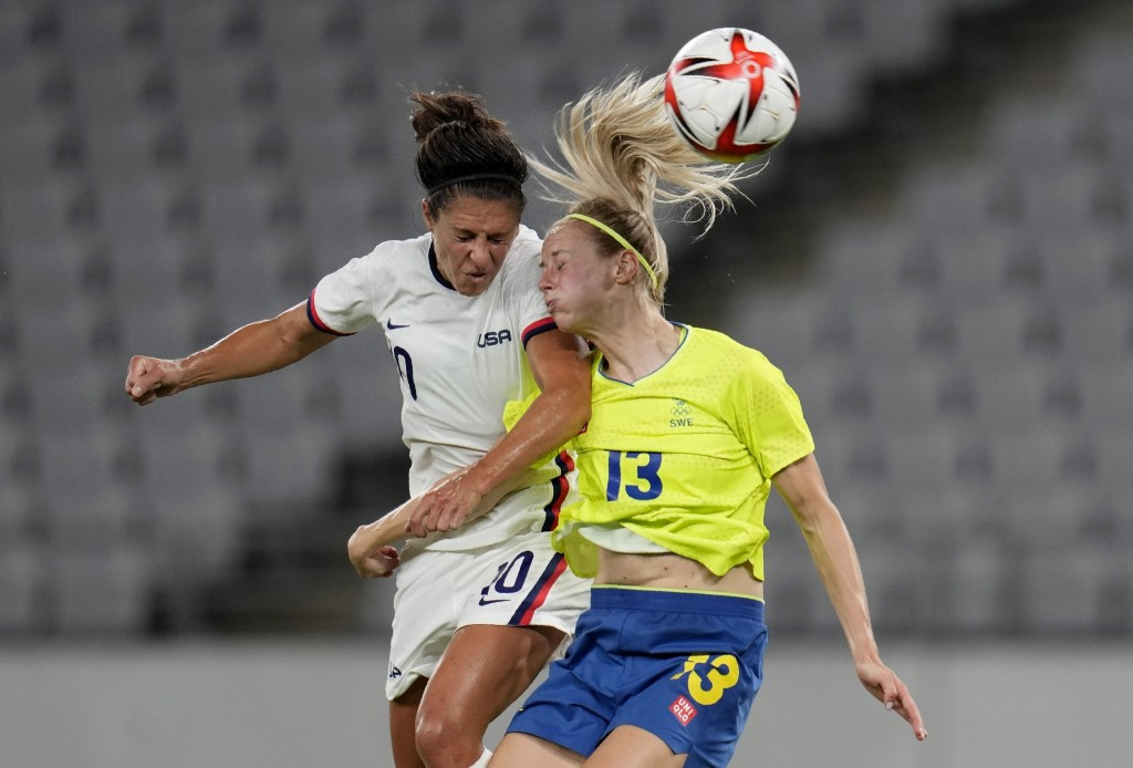 United States' Carli Lloyd, left, and Sweden's Amanda Ilestedt, right, go for a header during a women's soccer match at the 2020 Summer Olympics, Wedn...