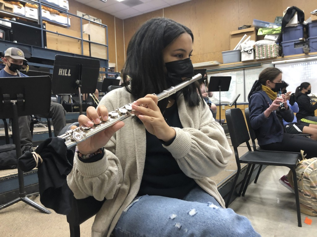 FILE - In this March 2, 2021 file photo, a student plays the flute while wearing a protective face mask during a music class at the Sinaloa Middle Sch...