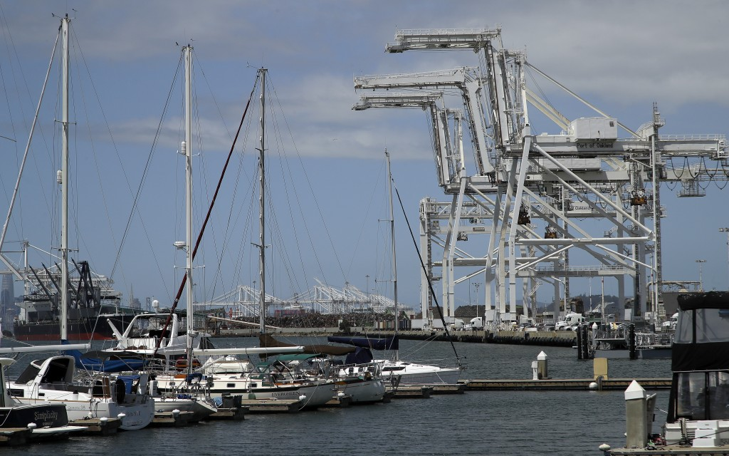 FILE - In this Friday, May 17, 2019, file photo, shipping cranes and a marina are near the Howard terminal area of the Port of Oakland in Oakland, Cal...