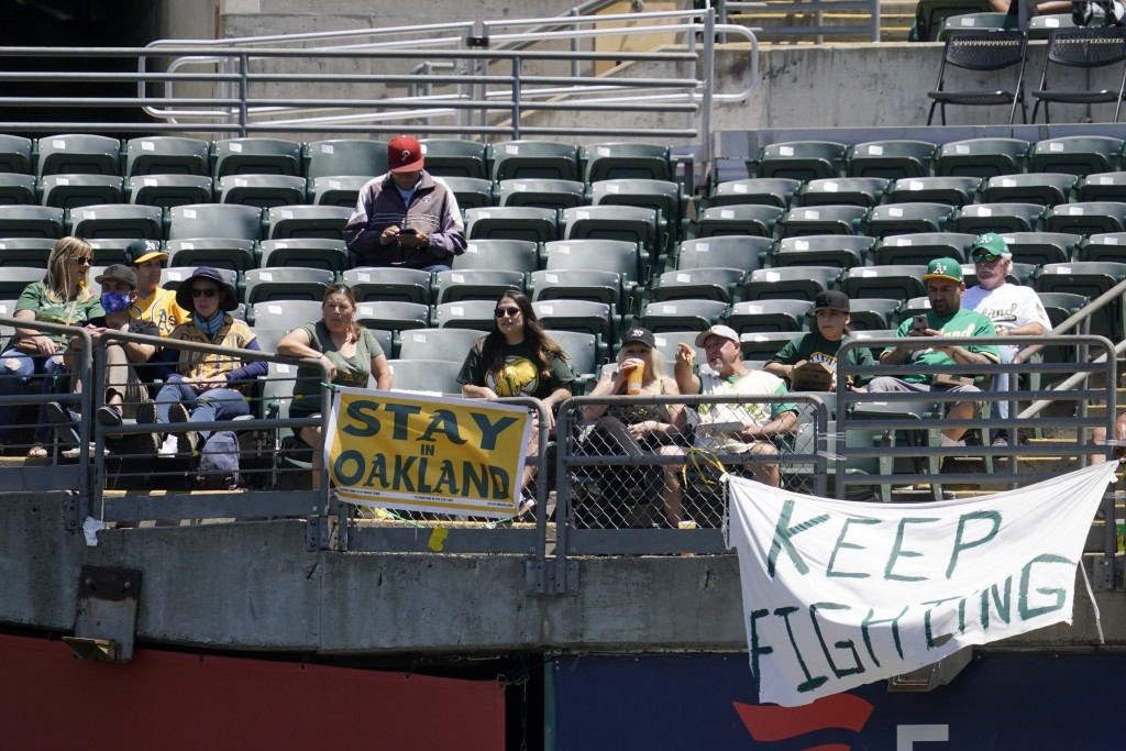 Fans sit behind a sign that reads Stay in Oakland during the first inning of a baseball game between the Oakland Athletics and the Los Angeles Angels ...