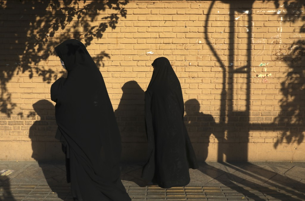 Women wearing protective face masks to help prevent the spread of the coronavirus walk on a sidewalk in southern Tehran, Iran, Tuesday, July 20, 2021....