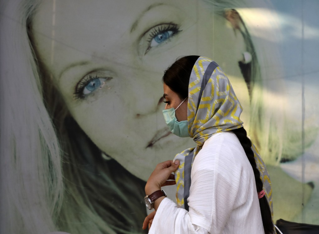 A woman wearing protective face mask to help prevent the spread of the coronavirus walks past an advertisement of skin care products in southern Tehra...