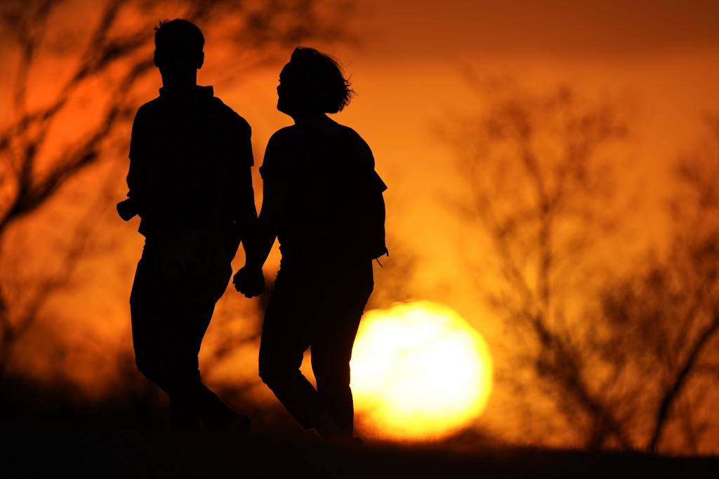 FILE - In this Wednesday, March 10, 2021 file photo, a couple walks through a park at sunset in Kansas City, Mo. According to a report released by the...